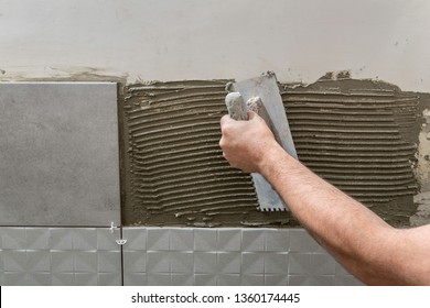 Hand of the tiler laying tile adhesive on the wall with a notched trowel. Close up.