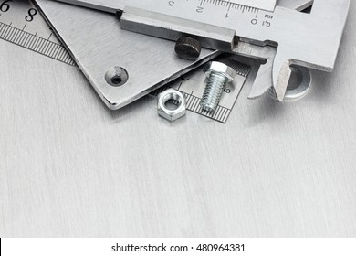 hand tools including vernier caliper, screws and bolt on scratched metal background