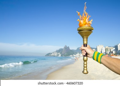 Hand of torchbearer athlete wearing Brazil colors sweatband holding sport torch on Ipanema Beach with Two Brothers Mountain on the skyline of Rio de Janeiro, Brazil