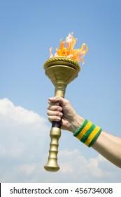Hand of torchbearer Brazilian athlete wearing Brazil colors sweatband holding sport torch against tropical blue sky
