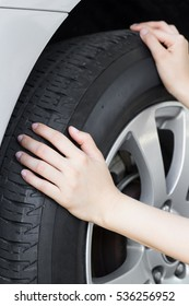 Hand touch on car tire, pressure check and inflating car tire in garage