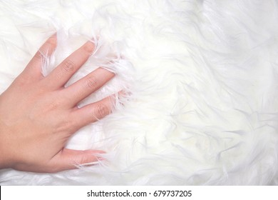 A hand touch on white fur carpet so gentle, background image.