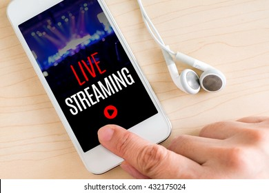Hand touch smart phone and ear phone with Live Streaming word on wood table ,Internet marketing concept.