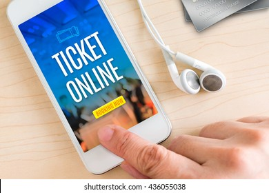 Hand touch smart phone and ear phone with Ticket online word on wood table ,Online payment concept.