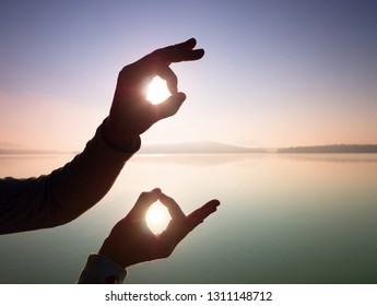 Hand touch Sun.  Palm shadow play with rising sun above lake and sun rays. Funny happy concept.