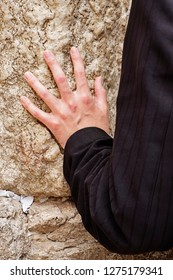 A hand touches the Wailing Wall in the Kotel during a prayer by an anonymous man in the Old City of Jerusalem.