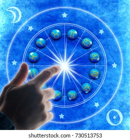 hand touching an astrology chart with all zodiac signs