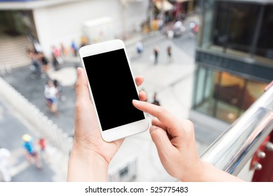 Hand touching blank screen mobile smart phone with city street outdoor in background