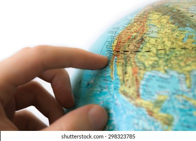 Hand touching globe on white background. The globe is marked with a black line, possibly planning a coast to coast journey from New York to Los Angeles. The west coast is in focus.