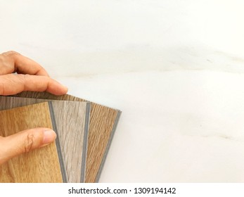 Hand touching luxury vinyl wood plank sheet for renovation design , flat lay with copy space