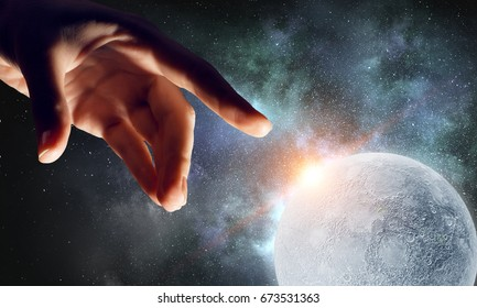 Hand touching the moon