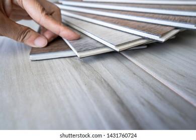 Hand touching on vinyl wood tiles sample stack on wooden ceramic tiles selecting for new floor tile design