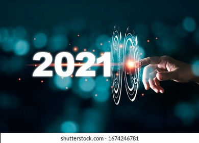 Hand touching pass thru infographic to 2021 year with blue bokeh and dark background. New year change concept. - Shutterstock ID 1674246781