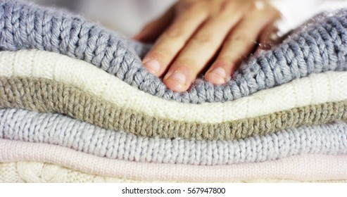 A hand touching a pile of colorful wool sweaters warm fluffy soft and comfortable to wear. cleaning concept, softness, warmth, cashmere, whiteness.