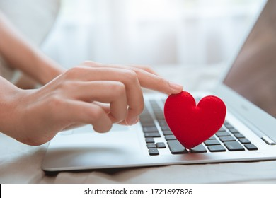 Hand touching red heart on laptop keyboard for flirt love chat or lover online text messenger for find date couple during stay home Coronavirus pandemic situation