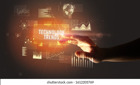 Hand touching TECHNOLOGY TRENDS inscription, new business technology concept