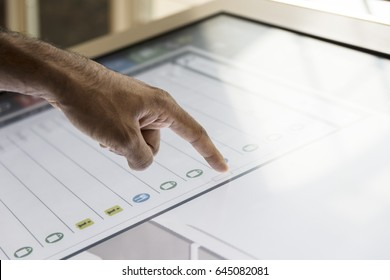 Hand touching touch screen. Asian, brown, hairy hand scrolling through list. Interactive screen