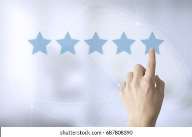 hand touching a touch screen interface with five star rating