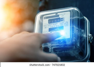 Hand is touching the transformer with copy space.Incorrect energy detection method.Watthour meter of electricity for use in home appliance.Electronics