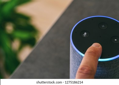 hand touching voice controlled speaker and personal Assistent at home