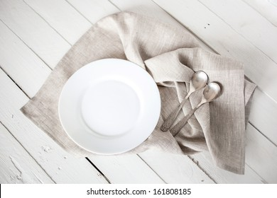 Hand towels with white plate and silver spoons on wood background.