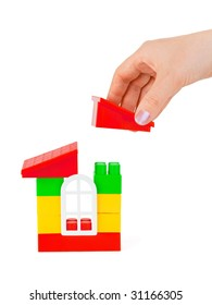 Hand and toy house isolated on white background
