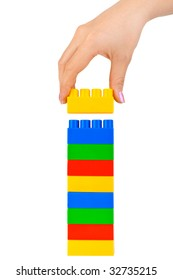 Hand and toy tower isolated on white background