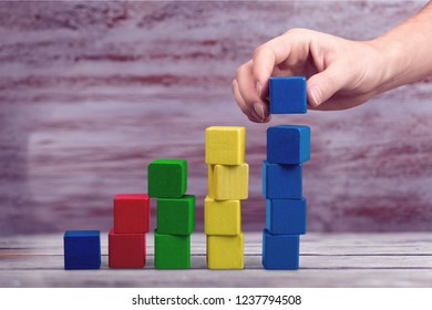 Hand with toy wooden blocks stack, towers of blank multicolor box cubes over white background