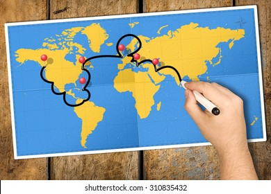 Hand tracking travel itinerary with black felt tip or marker on world map