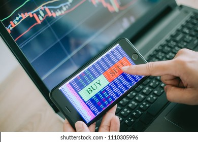 Hand of trader holding mobile phone touch screen showing buy and sell in Stock market order and blurred bakcground of laptop show financial chart, business trading concept