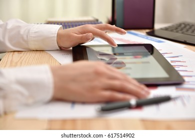 Hand of trader woman touching tablet screen with graph and charts. Business market concept