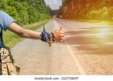 Hand Traveler hitchhiking. Young guy stops passing trucks on the highway. Summer time. Hitchhiking concept