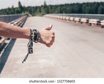 Hand Traveler hitchhiking. Young guy stops passing trucks on the highway. Hitchhiking concept