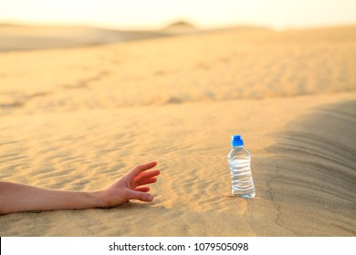 Hand try to catch the bottle of water on sand desert in hot temperature. Concept of to die of thirst.