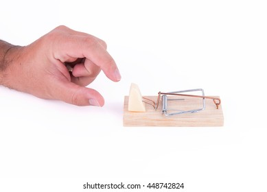 Hand trying to catch a piece of cheese on a mousetrap on white background