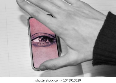 hand trying to close the screen of the smartphone with watching eye. smartphone is spying on the user. Smartphones overhear and spy, selective focus