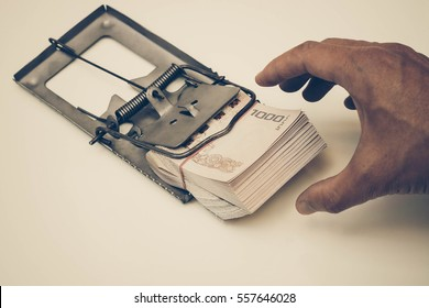 Hand trying to pick up a pile of Thai Baht banknotes from a mouse trap / Money trap / Debt