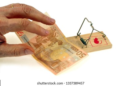 Hand trying to take a fifty euro note lying on a mousetrap on white background