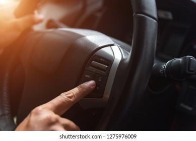 Hand tuning fm radio button in car panel.
