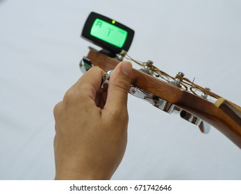 Hand tuning a guitar with tuner on white background
