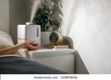 Hand turn on aroma oil diffuser on the bedside table at night at home, steam from the air humidifier. Ultrasonic technology, increase in air humidity indoors, comfortable sleeping conditions.