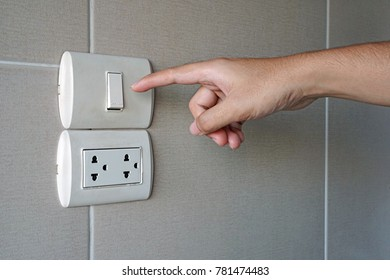 Hand turn on a power, Finger pushing light switch button with plug on ceramic tile wall in bathroom