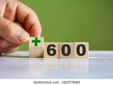 "The hand turn wooden block with plus sign and set text ""+600"""