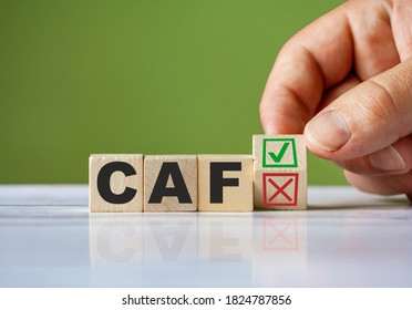 The hand turn wooden block with red reject X and green confirm tick as change concept of CAF. Word CAF conceptual symbol.