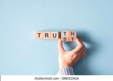"""Hand turned wood cube and changes the word """"Trust"""" to """"Truth""""."""