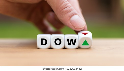 Hand is turning a dice and changes the direction of an arrow symbolizing that the Dow Jones Index is changing the trend and goes up instead of down (or vice versa)