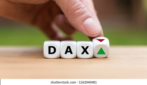 Hand is turning a dice and changes the direction of an arrow symbolizing that the German Stock Index DAX is changing the trend and goes up instead of down (or vice versa)