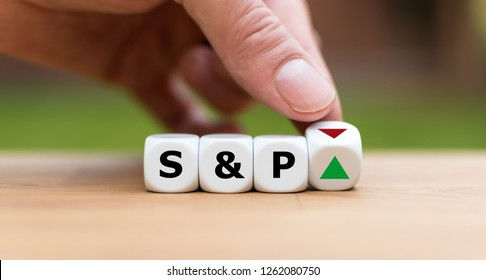Hand is turning a dice and changes the direction of an arrow symbolizing that the S&P500 Index is changing the trend and goes up instead of down (or vice versa)