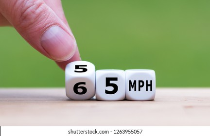 """Hand is turning a dice and changes the expression """"65 MPH"""" to """"55 MPH"""" as symbol to reduce the speed limit from 65 to 55 miles per hour"""