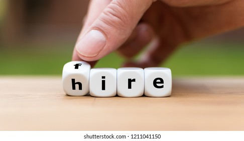 Hand is turning a dice and changes the word fire to hire